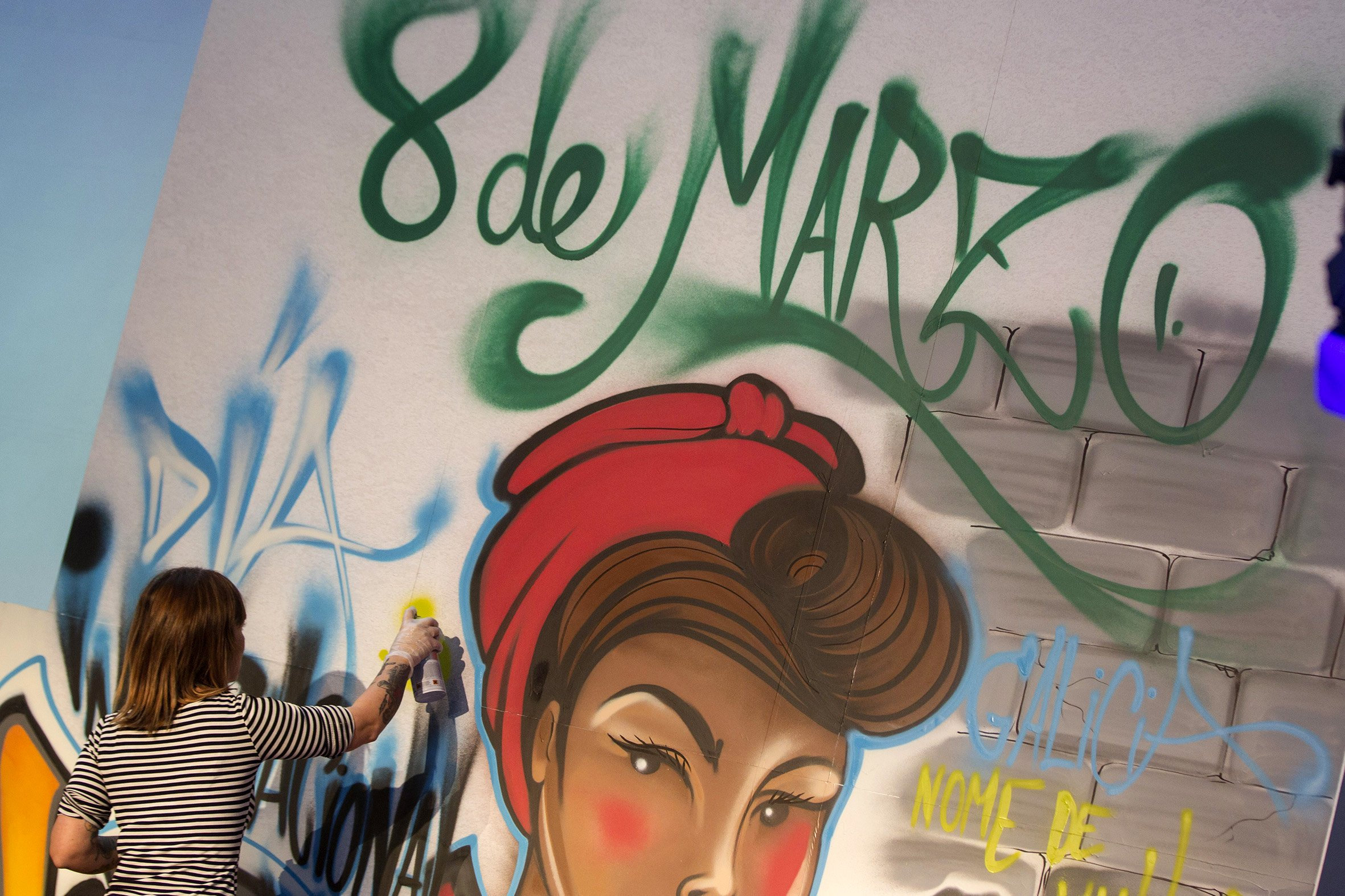 GRA241. SANTIAGO DE COMPOSTELA, 08/03/2016.- Una de las participantes en el acto institucional con motivo del Día Internacional de la Mujer, bajo el lema 'Con mulleres hay Galicia, hay ilusión, hay tenacidad, hay ideas, hay capacidad, hay identidad, hay pasión', firma en el graffiti del cartel commemorativo del acto. EFE/Óscar Corral